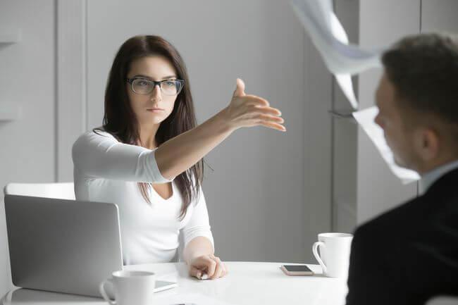 Женщина за ноутбуком протягивает мужчине руку