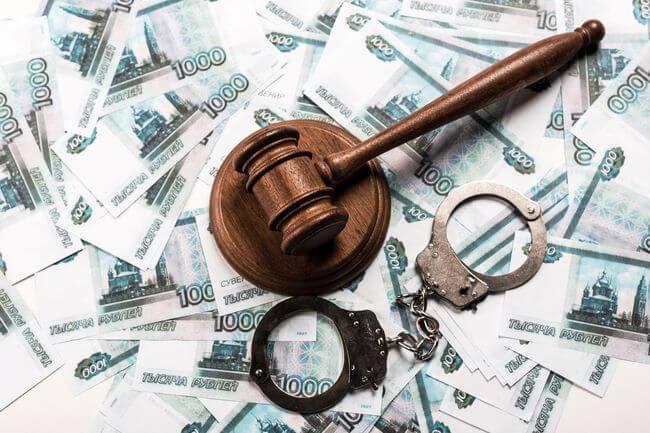Молоток судьи и наручники лежат на деньгах