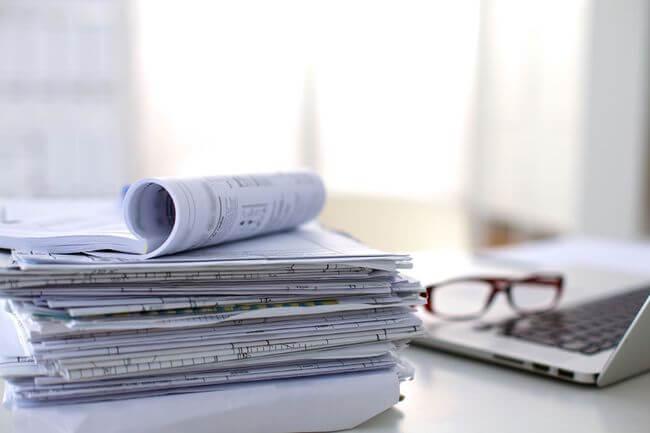 Стопка документов на столе рядом с ноутбуком