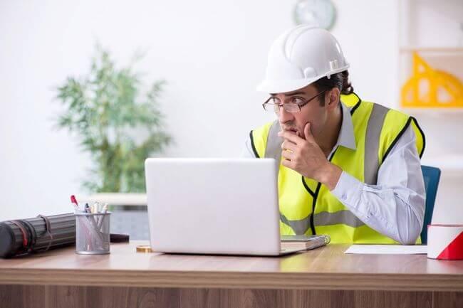 Строитель сидит за ноутбуком