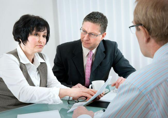 Женщина с двумя мужчинами обсуждает документы