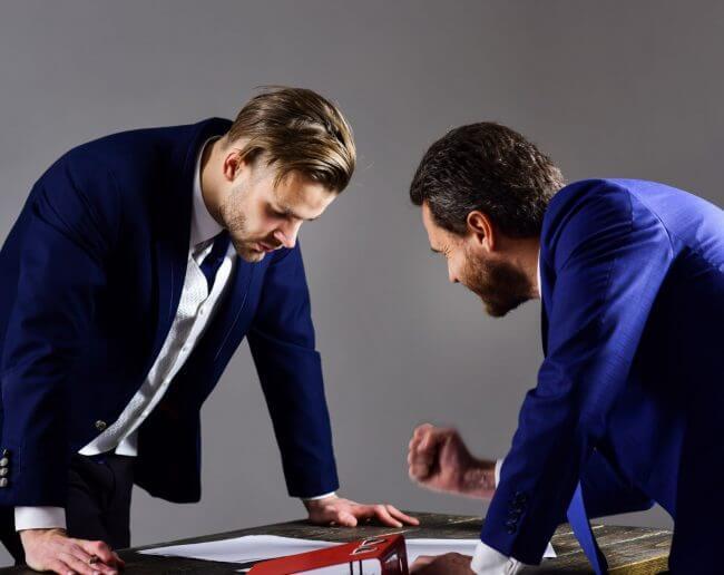 Двое мужчин изучают условия договора поставки