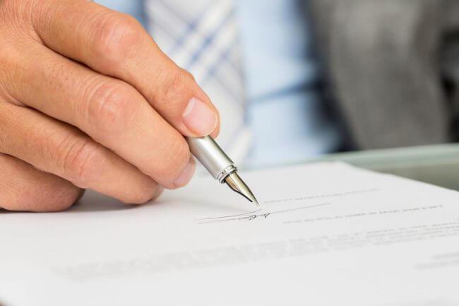 Мужчина ставит подпись на договоре поставки