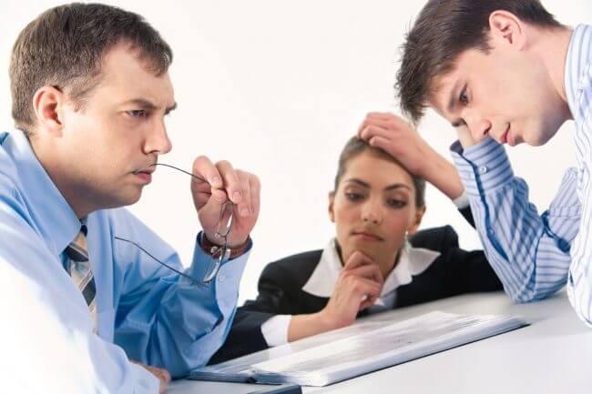 Двое мужчин и женщина думают над договором
