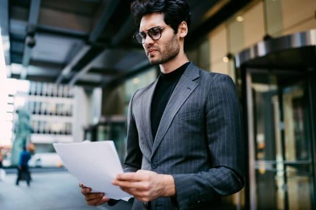 Мужчина в деловом костюме смотрим на договор поставки